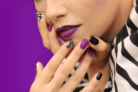 Black and white striped print on the nails and the makeup on the girl model closeup.Nail art.