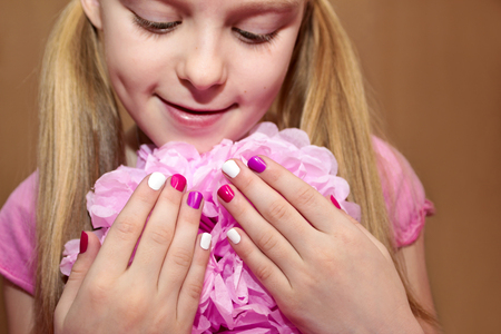 Pink white childrens manicure for the girl with the flower. Reklamní fotografie