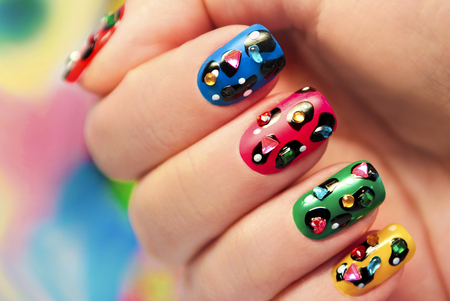 Colorful manicure close up with dots and rhinestones of different shapes and colors.