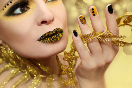 Festive yellow black manicure and makeup on a girl closeup on a yellow background.Nail art.