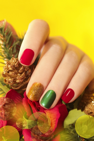 Multicolor manicure with red, green and yellow brilliant varnish for the nails on a yellow background with rose and Christmas tree. Stock Photo