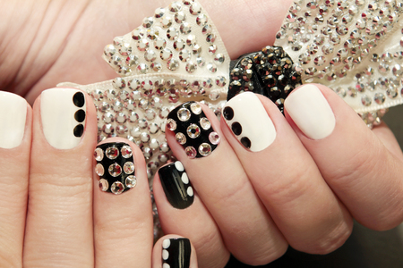 Black white manicure on a girl with actually and black dots closeup.