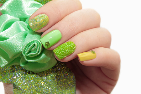 Pastel green manicure with sequins and rhinestones on a white background closeup.