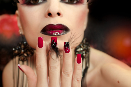 Black And Red Make Up With False Eyelashes And Long Red Nails