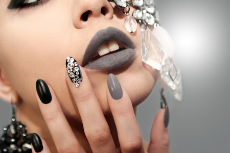 Black gray glam matte makeup and manicure with rhinestones and decoration on the girls face closeup.
