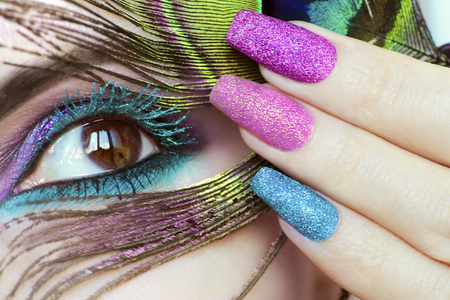 Colorful bright makeup on a brown eye close-up.Color turquoise mascara.Peacock eye.Nail extension.