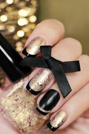 Black and gold French manicure with nail Polish in hand closeup.