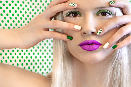 Nail design and makeup with green dots on a model on a background with dots.