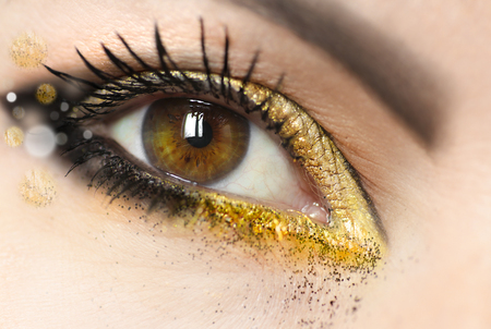 Womens makeup brown green eyes with gold eye shadow, dark eyeliner and a glitter close-up.Fashionable makeup.