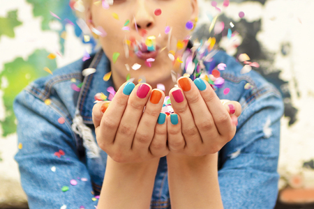 Fashionable girl with bright colorful nail designs blows confetti in her hands.Nails art.Color manicure. Banco de Imagens