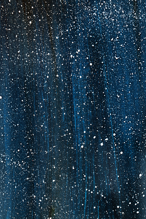 Dark blue background with white dots of white paint.