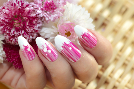 French oval manicure with a striped gradient in pink tones. Summer flower nail design close-up.