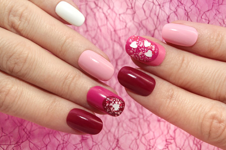Colorful oval pink and burgundy manicure with hearts. Stok Fotoğraf