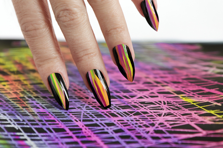 Colorful bright manicure with black lacquer.Nail art. Creative nail design on color background.