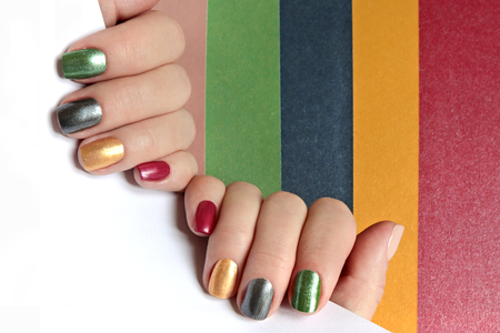 Multi-colored mother of pearl nail art. Nail design. Red, green, gray, beige, Golden yellow nail Polish.