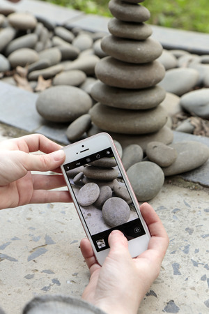 Hands hold pictures of the pebble pyramid. Passion and desire to take pictures.