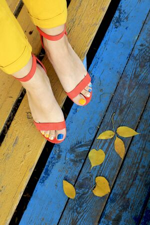 Multicolored autumn pedicure in orange sandals with yellow leaves on a blue wooden background close-up.