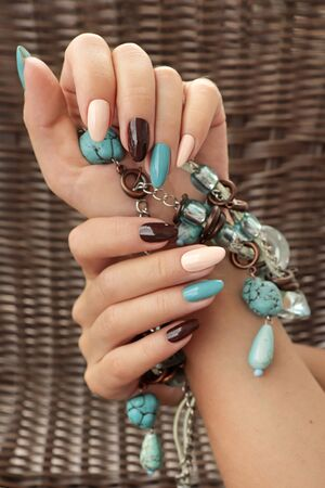 Oval multicolored manicure on a womans nails. Nail design with turquoise, brown, light beige nail Polish.