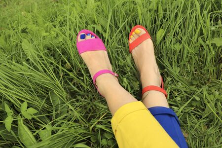 Colorful bright pedicure in different pink and orange sandals and different blue and yellow pants on a background of green grass. Fashionable summer nail art.