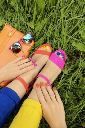 Colorful bright manicure and pedicure in different pink and orange sandals, and different blue and yellow pants on a background of green grass with glasses and a bag. Fashion accessories and summer nail art.