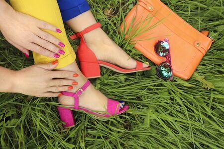 Manicure e pedicure luminose colorate in diversi sandali rosa e arancioni e diversi pantaloni blu e gialli su uno sfondo di erba verde con occhiali e una borsa. Accessori moda e nail art estive.