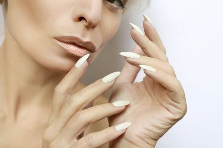 Portrait of a woman with clean healthy skin and a long manicure