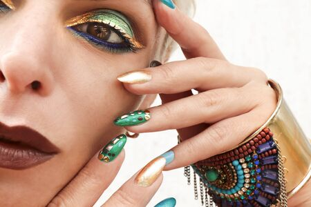 Multi-colored fashionable makeup and manicure in turquoise Golden blue and brown tones. Nail art with metal rhinestones on the nails. Imagens