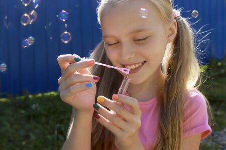 A young smiling beautiful blonde girl inflates soap bubbles in the summer on a blue background. Fashionable multi-colored children nail art, nail design.