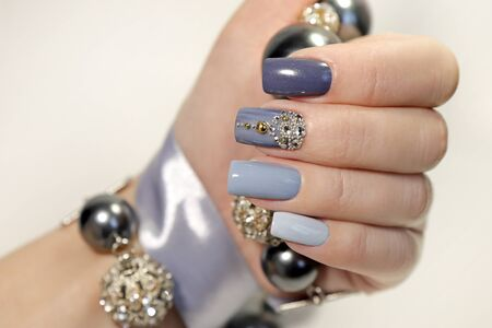 Fashionable gray blue manicure on square shaped nails. Nail art with rhinestones on a light background with decoration.