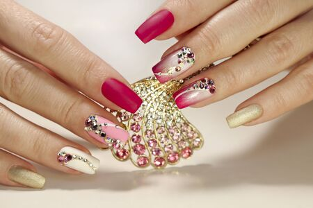 A luxurious manicure with a pink matte finish for nails and a gradient from white with gold to pink nail Polish. Nail art with various shaped rhinestones and colors.