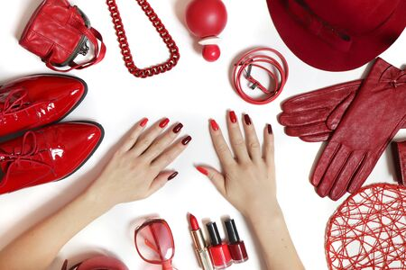 A diverse collection of clothing and accessories in red on a white background. Fashionable decorative cosmetics and nail art on women's hands from light red to dark nail Polish.