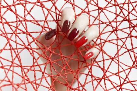 Fashionable red nail Polish color from light to dark on a rectangular shape.Nail art.