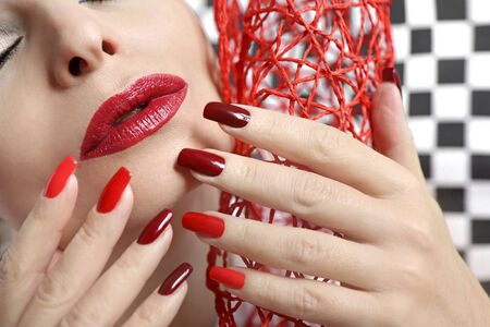 Red fashionable makeup and manicure on long square nails. Creative nail art.