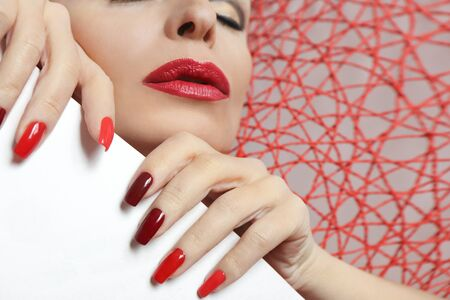 Fashionable makeup and manicure in dark red and light shades of nail Polish. Creative nail art on a young woman on a bound background.