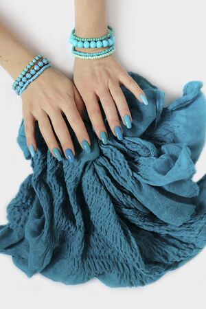 Fashionable oval long nails with different shades of nail polish from light blue to turquoise. Creative manicure on female hands with bracelets and a scarf.