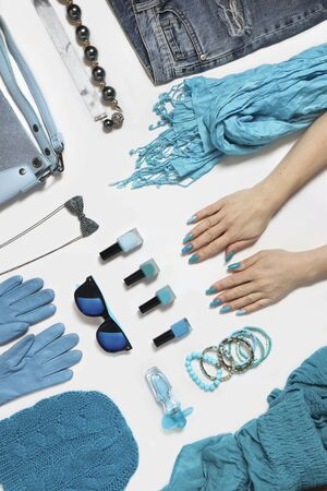 Fashionable blue accessories, decorative cosmetics and other stylish items on a white background. Creative manicure on long oval nails with bracelets.