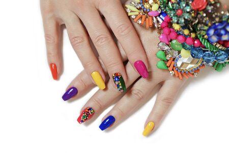 Manicura saturada brillante creativa en uñas largas con pedrería. Arte de uñas en manos de mujeres sobre un fondo blanco con bisutería.