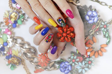 Creative bright saturated manicure on long nails with rhinestones. Nail art on women's hands on a white background with costume jewelry.
