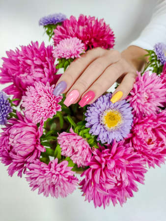 Fashionable design of bright pink, yellow and lilac on the nails of a girl with a composition of asters.