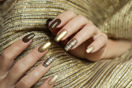 Fashionable manicure with a matte Golden color of nail Polish and brown on a long nail shape.