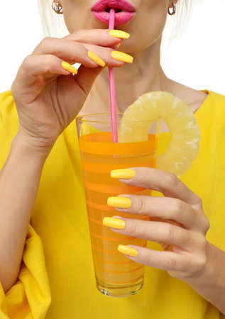 Young woman drinking pineapple juice with joy. Trendy manicure with yellow nail polish on a long form. Фото со стока