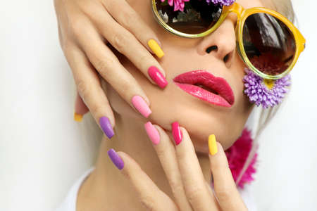 Fashionable multi-colored makeup and manicure on long nails of a girl with asters and glasses.