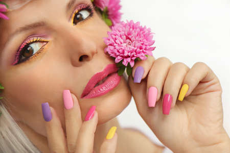 Fashionable multi-colored makeup and manicure on long nails of a girl with asters.
