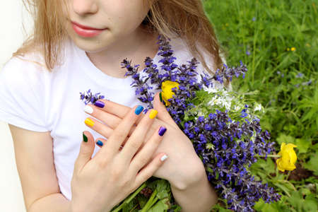 Beautiful blonde girl holding a bouquet of meadow wildflowers in summer.Children's fashionable manicure.