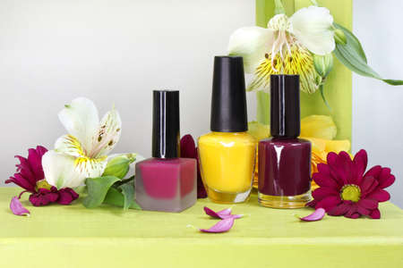 A set of three nail polishes in yellow, Burgundy, cherry glossy and matte colors with flowers.
