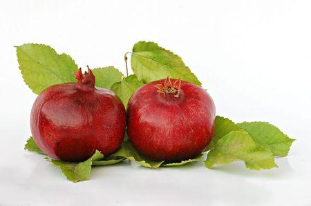 superfruit: Ripe pomegranates on green leaves isolated on white background Stock Photo