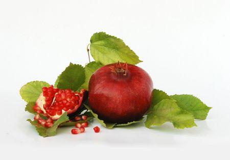 Pomegranates on green leaves isolated on white background photo