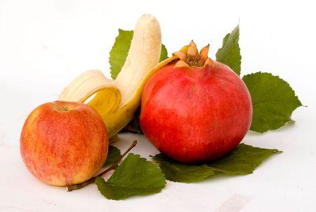 superfruit: Pomegranate, apple, and banana on leaves