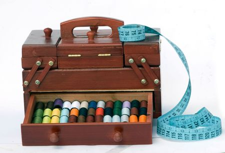 Wooden drawers with spools of colorful threads and measuring tape photo