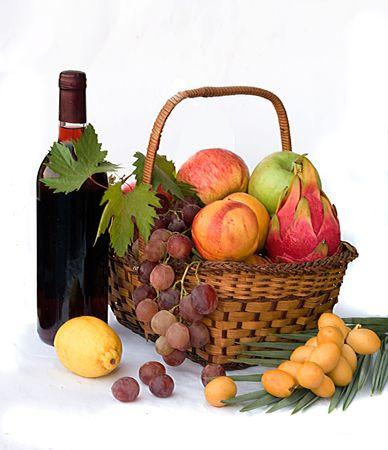 Wine bottle and bunch of fresh fruits isolated on white background photo
